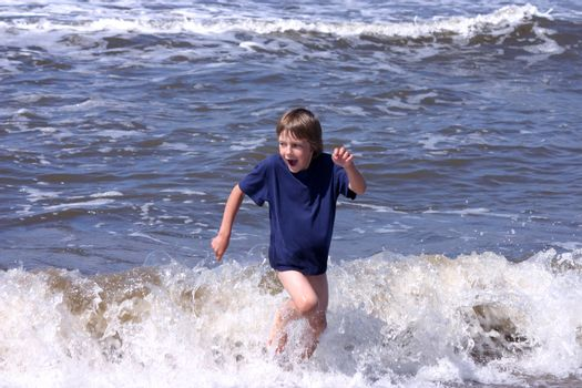 Happy 6-8 years boy playing on the beach and trying to escape waves