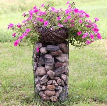 Basket full of petunias standing on tje decorative pile of stones