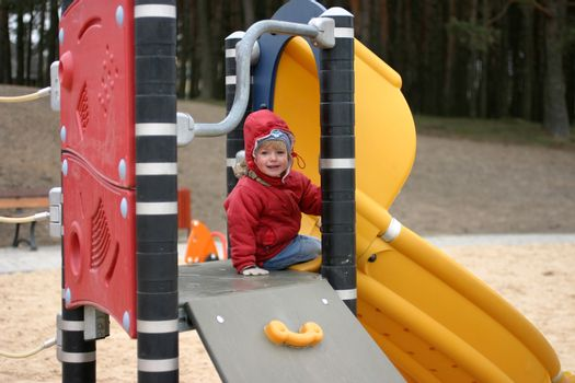 Two years old girl sitting on the jungle gym at cold spring day and smiling