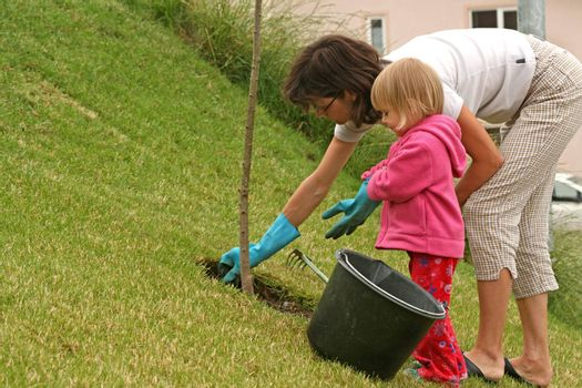 Mother and her little daughter gardening