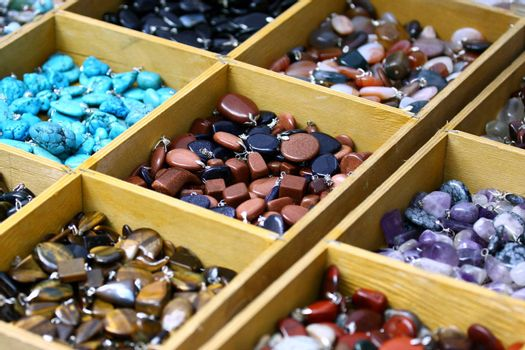 Multicolored trinket stones on sale in different boxes