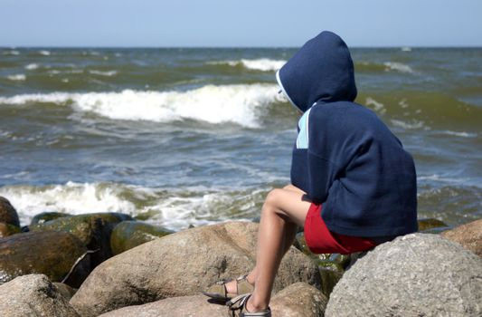7-8 years boy sitting on the rocks and watching the sea