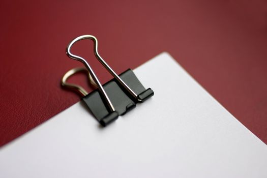 Macro view of paper clip with fragment of stack of white paper