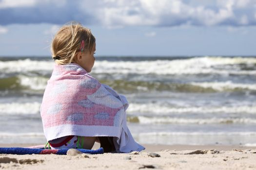 Little girl sitting on the beach and looking at the sea