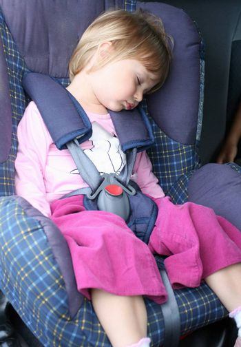 Young girl rests in the car seat