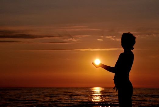 Woman silhouette at sunset as like holding the sun