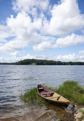 Natural summer scenery with lake, nice clouds and single moored wooden boat