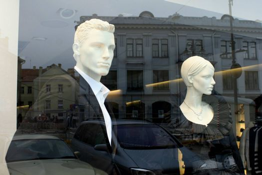 Luxury boutique window display with two mannequins and reflections