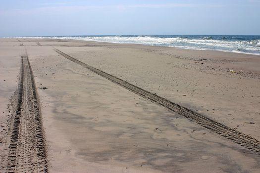 Wheel tracks on the empty beach sand