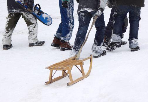 Boys climbing up the snowy hill with slegde and snowboard, focus on slegde