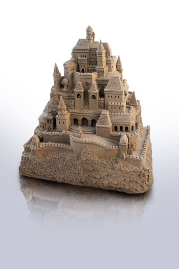 large isolated sandcastle with many towers and crenels