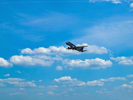 A Commercial Airliner Taking Off into a Partly Cloudy Blue Sky
