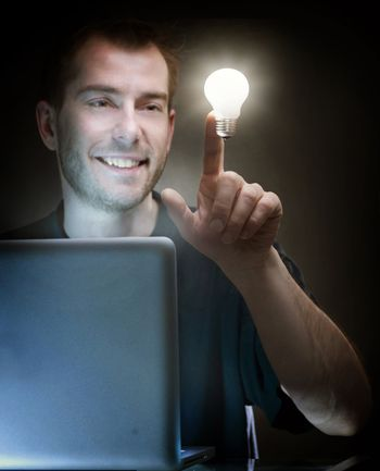 Young Man With Laptop And Idea Light Bulb