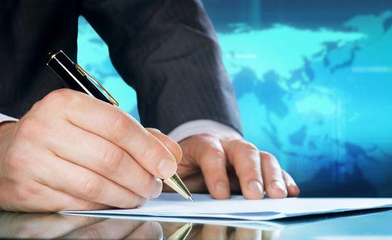 Businessman's hand with a pen. International business concept