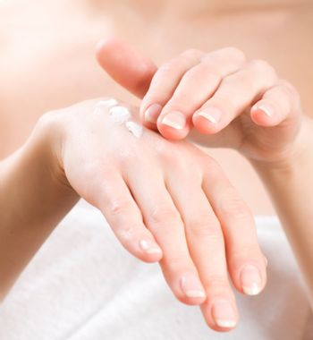 Female applying moisturizer to her Hands after bath. Skincare co