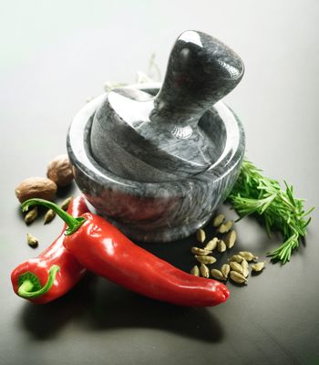 Mortar With Pestle And Herbs. Over Black Background