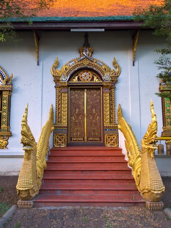 Golden dragons in front of carved doors of asian temple, Wat Chiang Man, Chiang Mai, Northern Thailand