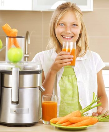 Happy Girl drinking fresh carrot and apple juice. Juice Extracto