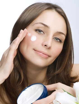 Beautiful Young Woman applying facial moisturizer. Skincare