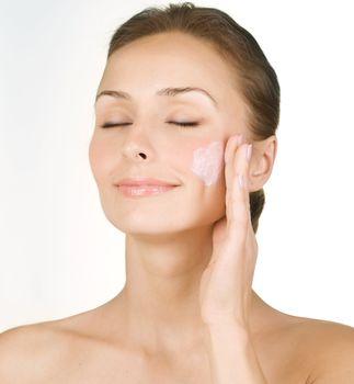 Beautiful Young Woman Applying Facial Moisturizer. Skincare Conc