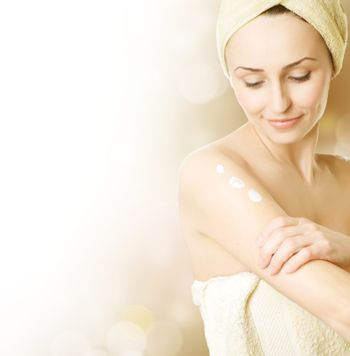 Beautiful Young Woman Applying Moisturizer. Skincare Concept