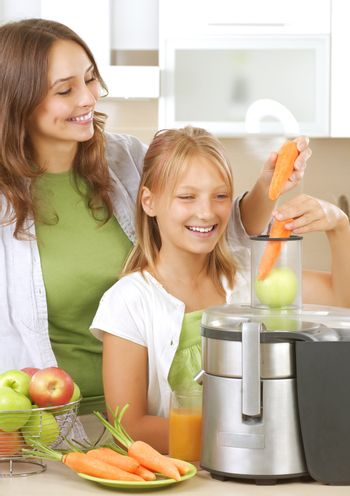 Happy Mother with Daughter eating Healthy food. Kitchen. Healthy