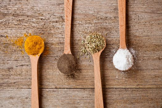 curry, pepper, oregano and cooking salt in wooden spoons on rustic wooden background