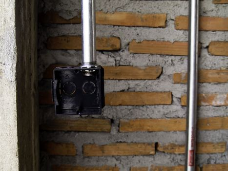 Plastic box for electrical work with brick wall