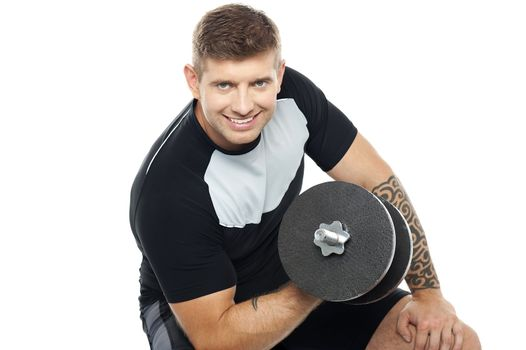 Muscular man working out with barbell