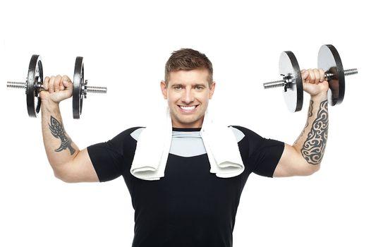 Young bodybuilder exercising, toning his biceps