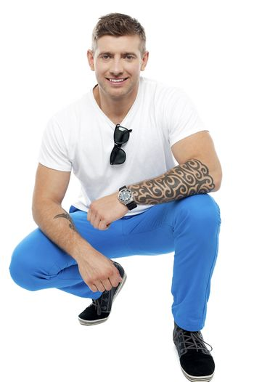 Tattooed man in squatting position