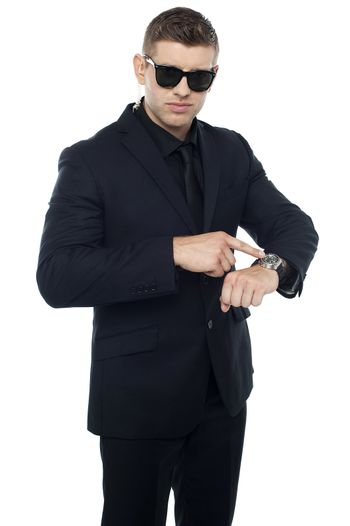 Security official pointing at his watch