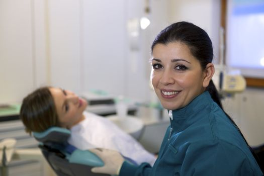 Doctor during visit of woman in dental clinic, portrait of female dentist looking at camera and smiling