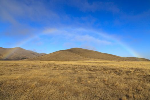rainbow bridge over the dry grassland at the south island of new zealand