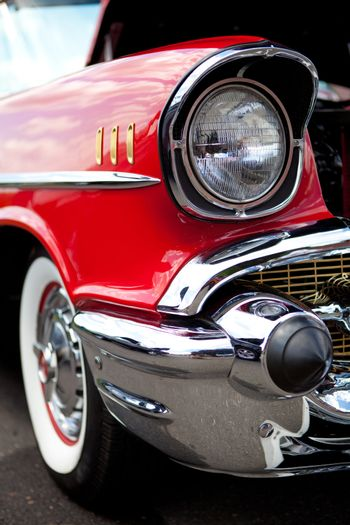 A closeup of the headlight and front bumper on a vintage American automobile.