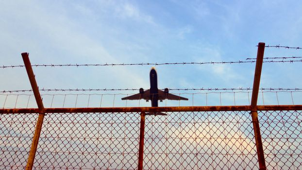 Airplane is flying up over a metal fence