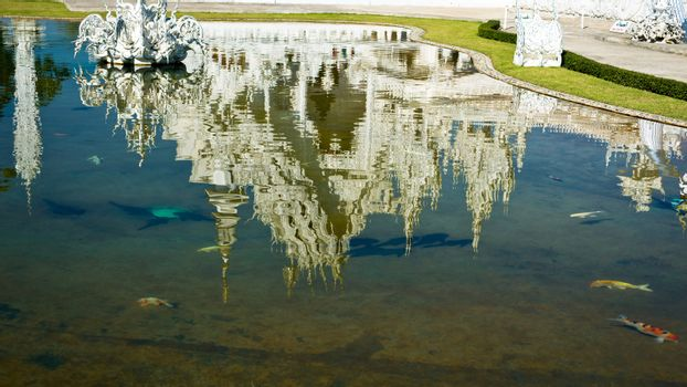 Reflection of white temple Wat Rong Khun in a pond with fishes. Wat Rong Khun is a contemporary unconventional Buddhist temple in Chiang Rai, Chiangmai province, Thailand. It is designed in white color.