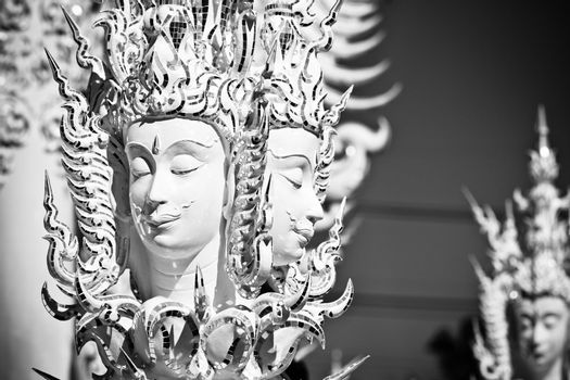 Statue of mythological head in Wat Rong Khun. Wat Rong Khun is a contemporary unconventional Buddhist temple in Chiang Rai, Chiangmai province, Thailand. It is designed in white color.