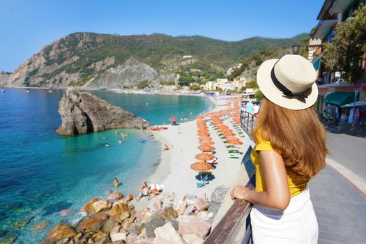 Summer holiday in Italy. Back view of young woman with hat in Monterosso al Mare village, Cinque Terre, Italy.