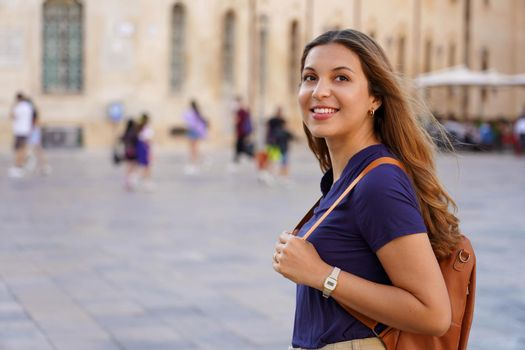 Cultural trip in Europe. Attractive girl strolling alone in historic european city.