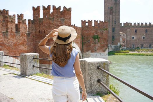 Promenade riverside in Verona, Italy. Back view of lady walking along promenade with medieval fortress Castelvecchio castle and bridge on the background.