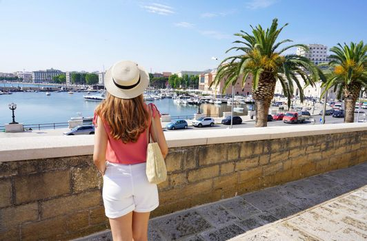 Rear view of young woman looking at harbour and cityscape of Bari, Italy