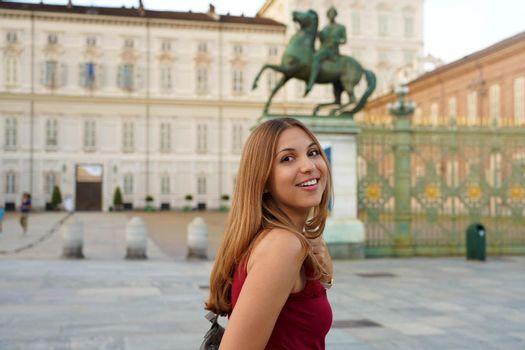 Travel in Europe. Attractive girl in Italy with Royal Palace of Turin on the background.