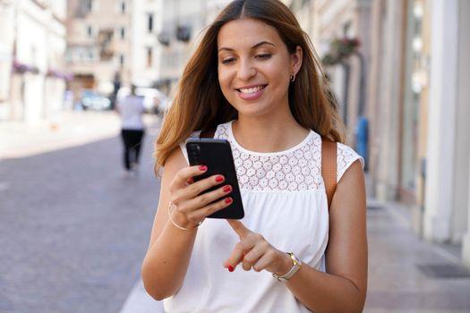 Brazilian dynamic girl using smartphone walking in street