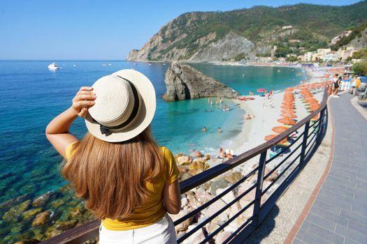 Italian Riviera. Pretty girl with hat on promenade looking at Monterosso al Mare village on Cinque Terre, Italy