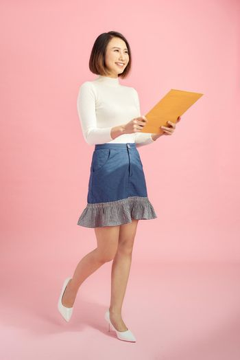 Full-length portrait of businesswoman with folder, isolated on pink. Concept of leadership and success