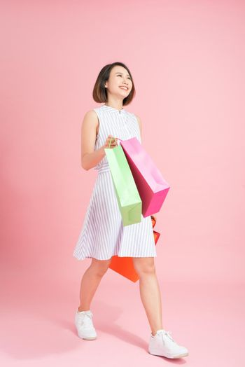 Excited female shopaholic with shopping bags