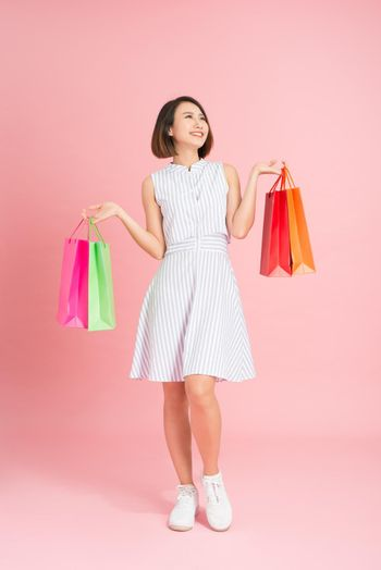 pretty glamor woman in a light blue dress on a pink background shopping