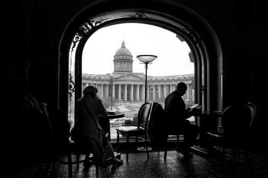 Silhouette of woman and man reading books in a cafe in bookstore in Saint Petersburg, Russia