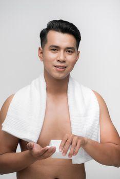 Attractive Vietnamese man applying moisturizer to face